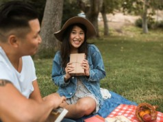 asian couple on a picnic ground with books