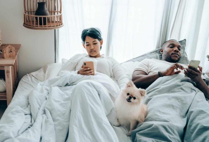 multiracial couple surfing mobile phones lying in bed with dog after awakening