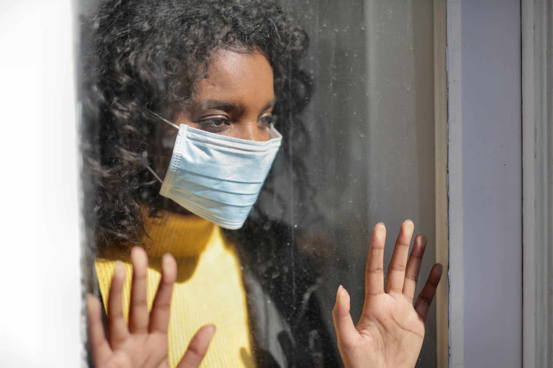 serious young ethnic lady in medical mask standing near window and looking away on street