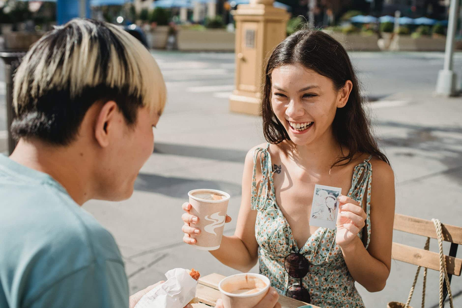 happy ethnic woman showing photo to boyfriend